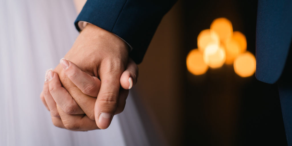 A happy couple holding hands at a wedding.