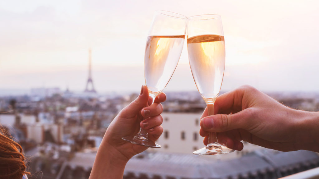 A happy couple raising champagne glasses in in Paris.